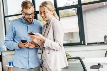 smiling young business colleagues using smartphones and talking at workplace