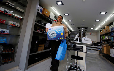 Palestinian customer carries an appliance he bought in an electronics store in Hebron, in the occupied West Bank