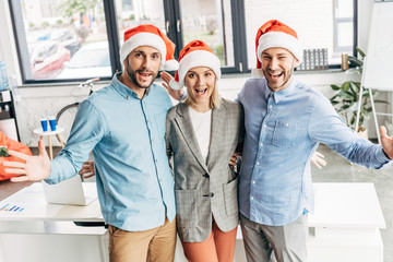 cheerful young business team in santa hats smiling at camera in office