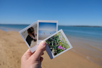 Hand holding instant photos taken at the beach