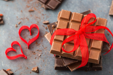 Valentine's day. Chocolate bars decorated red ribbon and hearts on a gray background