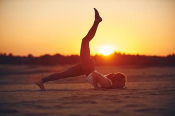 Young woman is doing yoga asana Eka Pada Ashtanga Namaskarasana - eight limbed salutation pose in the desert at sunset