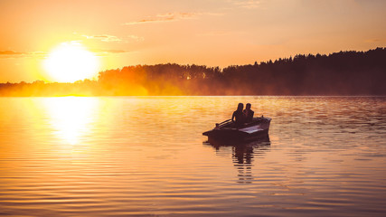 Couple in love ride in a rowing boat on the lake during sunset. Romantic sunset in golden hour. Happy woman and man together relaxing on water nature around
