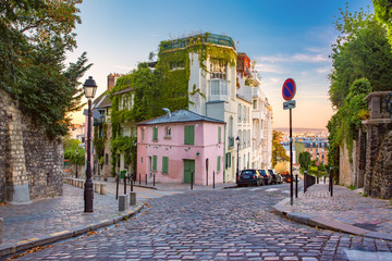 Acrylic Prints Historical buildings Cozy old street with pink house at the sunny sunrise, quarter Montmartre in Paris, France