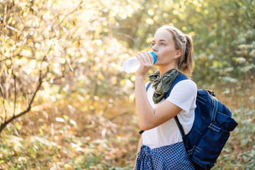 Young beautiful woman drinking water in sport bottle on hiking