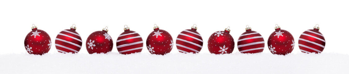 Red christmas balls in a row isolated on snow, Christmas decoration