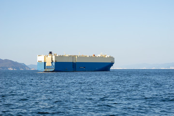 Large White and blue Roll-on/roll-off (RORO or ro-ro) ships or oceangoing vehicle carrier ship anchor in the open sea. Roro ship designed to carry wheeled cargo such as cars, trucks, trailers, etc. Wall mural