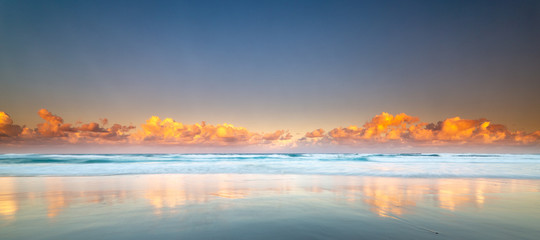 Reflection of clouds at sunset at the beach