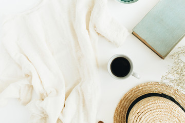 Female office desk with coffee, book, straw hat, flowers and blanket on white background. Flat lay, top view.