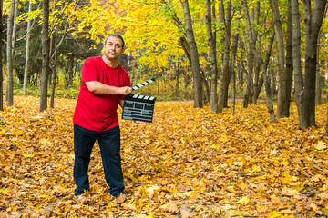 The man in the red Jersey keeps clapping Board on the background of yellow leaves in the autumn Park