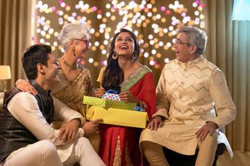 Family sitting together and laughing with gifts on the occasion of Diwali