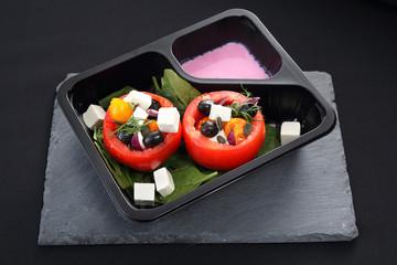 Danie gotowe, pomidory faszerowane z różowym sosem jogurtowym. Pomidory faszerowane oliwkami, serem feta, szpinakiem podane w pojemniku plastikowym.