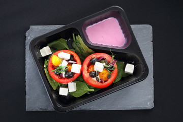 Catering dietetyczny, pomidory faszerowane warzywami z sosem jogurtowym. Pomidory faszerowane oliwkami, serem feta, szpinakiem podane w pojemniku plastikowym.