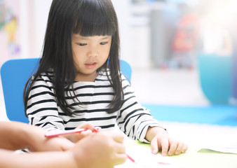 Asian child cute or kid girl smile and study learning for coloring paint on white paper with teacher or mother at nursery or children pre school and kindergarten on soft focus and sunlight on window