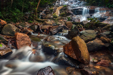 Beautiful tropical waterfall in lush surrounded by green forest.wet rock and moss.selective focus shot.
