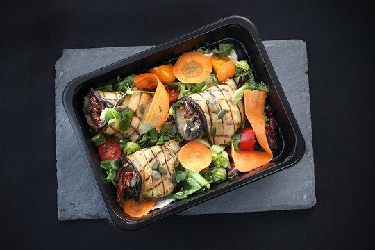 Lunch box. Roladki z grillowanego bakłażana z suszonymi pomidorami i serem podane na sałacie i marchewce zapakowane w pojemnik na żywność.
