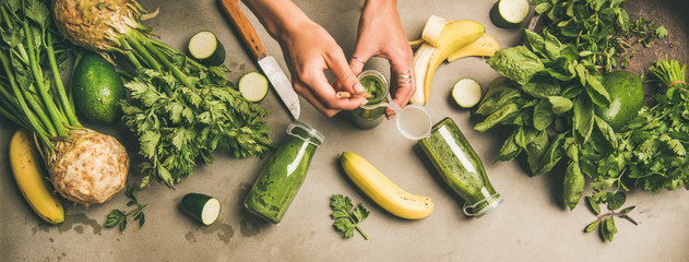 Making green detox smoothie. Flat-lay of ingredients for making smoothie and female hands holding bottle with straw over concrete background, top view. Weight loss, healthy food concept