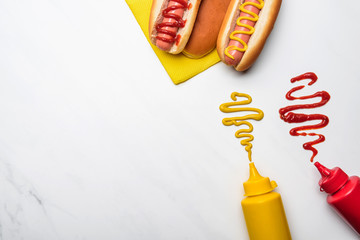 top view of delicious hot dogs with mustard and ketchup on white marble surface