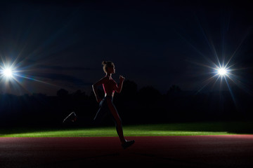 Silhouette of woman running forward in darkness on stadium.