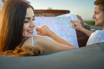 Adorable woman smiling, man holding map while sitting in cabriolet.