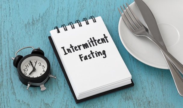 Intermittent fasting concept on blue table