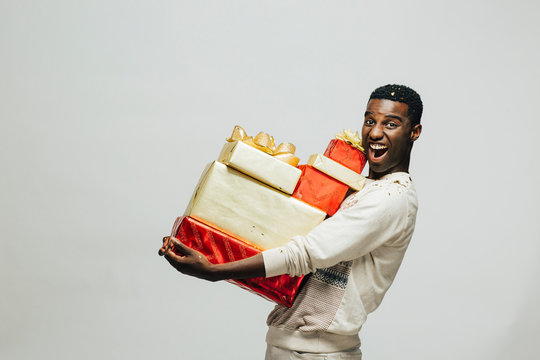 Portrait of an excited young man carrying many gifts , isolated on white studio background