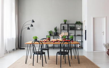 Black chairs at wooden table with food in grey dining room interior with plants and lamp. Real photo