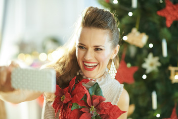 smiling woman with red poinsettia taking selfie with phone