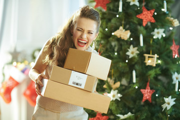 smiling modern housewife near Christmas tree catching parcels