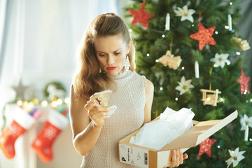 woman near Christmas tree looking at broken dish from parcel