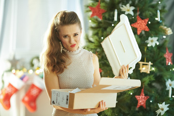 unhappy woman with broken dish from parcel near Christmas tree