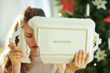 stressed trendy woman with broken dish near Christmas tree