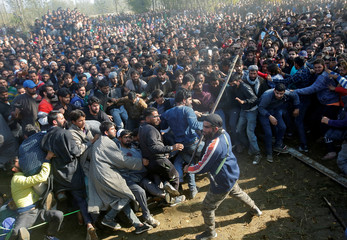 A suspected militant wields a stick to keep people away before offering a gun salute during the funeral procession of Sabzar Ahmad Sofi, a suspected militant, in south Kashmir's Sangam town