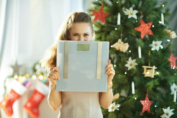 modern woman near Christmas tree hiding behind weight scales