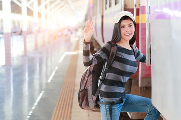 young traveler woman with backpack getting on the train