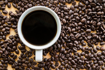 Black coffee in a white coffee cup with coffee beans background