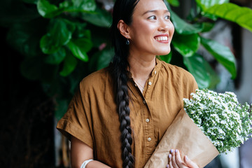 Pretty Asian woman standing outdoors and holding fresh flowers.
