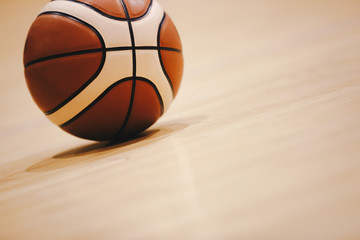 Basketball on Wooden Court Floor Close Up with Blurred Arena in Background. Orange Ball on a Hardwood Basketball Court