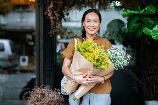 Portrait of smiling Asian woman standing outdoors, holding flowers and looking at camera.
