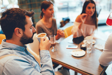 Young man enjoys coffee with friends in a cafe