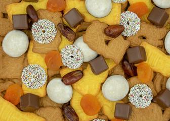 Weihnachtshintergrund aus verschiedenen Sorten von Weihnachtsplätzchen,  Süssigkeiten, Datteln und getrockneten Aprikosen