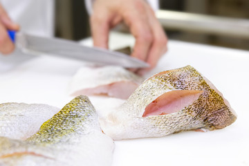 A chef scoring a zander fish fillets with a knife. White chopping board.