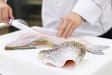 Foto op Canvas Vis A large zander fish fillet lying on a white chopping board. A chef filleting a fish in the background.