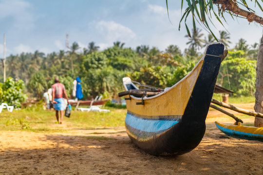 Tropical beach with palms and fishing boats in Mirissa, Sri Lanka with fisherman on the background