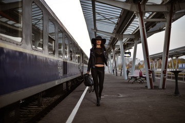 Young sexy woman dressed in black posing on a train station pier.