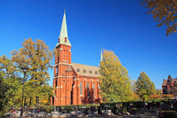 old church made of orange bricks and cemetery on sunny autumn day in Trinec, Czech Republic