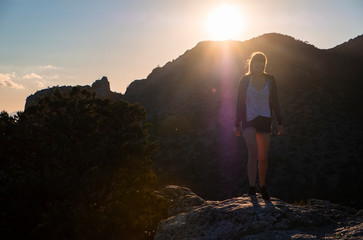 Girl in the mountains on top at sunset or dawn