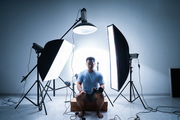 male photographer in photography studio surrounded by lighting equipment