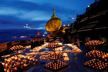 Buddhist pilgrims light candles around the Golden Rock or Kyaikhtiyo Pagoda to celebrate the full moon festival in Kyaikto