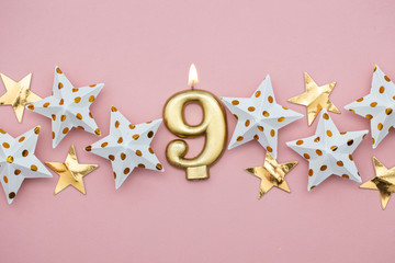 Number 9 gold candle and stars on a pastel pink background